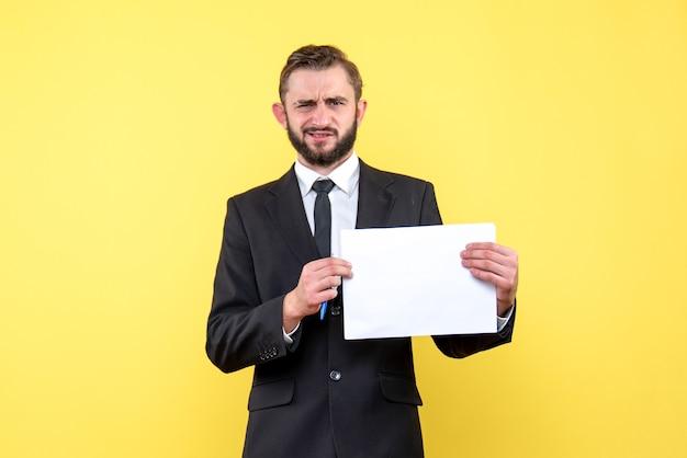 Il punto di vista frontale dell'uomo d'affari del giovane in un vestito è sconcertato che rigorosamente fa un interrogatorio sul giallo Foto Gratuite