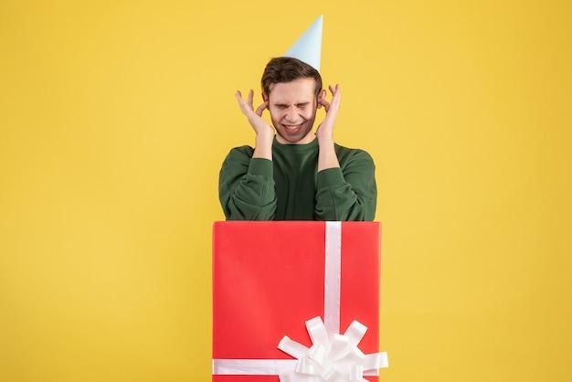 Giovane vista frontale che chiude le orecchie con le dita in piedi dietro il grande giftbox su giallo Foto Gratuite