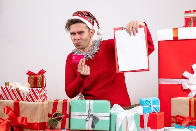 크리스마스 선물 주위에 앉아 카드와 클립 보드를 들고 전면보기 젊은 남자 무료 사진