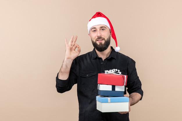 Front view of young man holding christmas presents on pink wall Free Photo