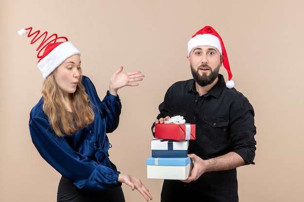Front view of young man holding christmas presents with woman on pink wall Free Photo