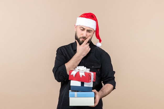 Front view of young man holding holiday presents on pink wall Free Photo