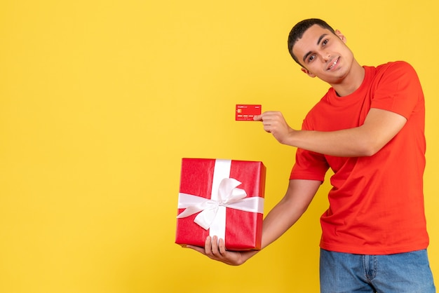 Front view of young man holding present and bank card on the yellow wall Free Photo
