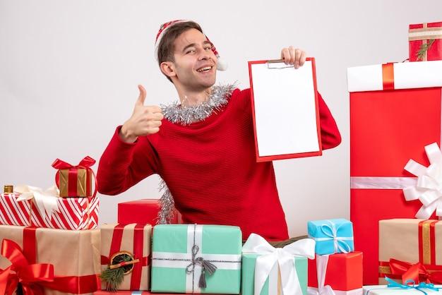 크리스마스 선물 주위에 앉아 가입 엄지 손가락을 만드는 전면보기 젊은 남자 무료 사진