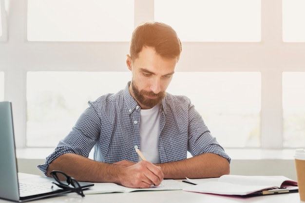 Front view young man at office writing Free Photo