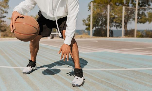 外でバスケットボールをしている正面図の若い男 無料写真