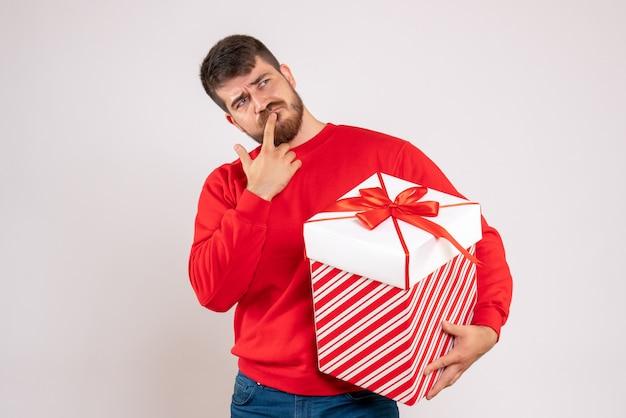Vista frontale del giovane in camicia rossa che tiene regalo di natale in scatola pensando sul muro bianco Foto Gratuite