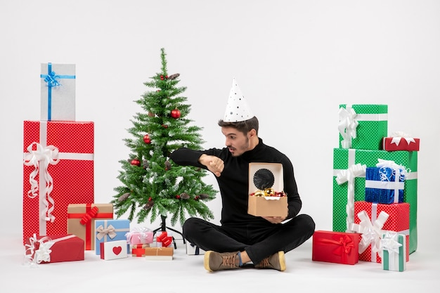 Front view of young man sitting around holiday presents holding tree toys checking time on white wall Free Photo