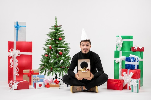 Front view of young man sitting around holiday presents holding tree toys on a white wall Free Photo