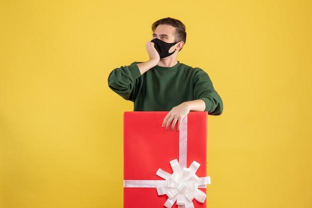 Giovane di vista frontale che pensa a qualcosa che sta dietro il grande giftbox su giallo Foto Gratuite