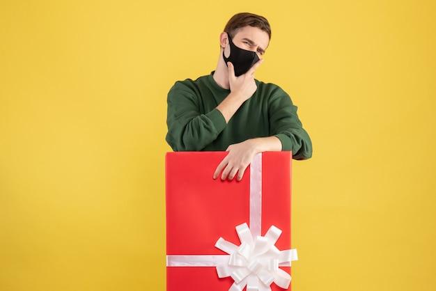 Giovane di vista frontale che pensa qualcosa che sta dietro il grande giftbox su colore giallo Foto Gratuite