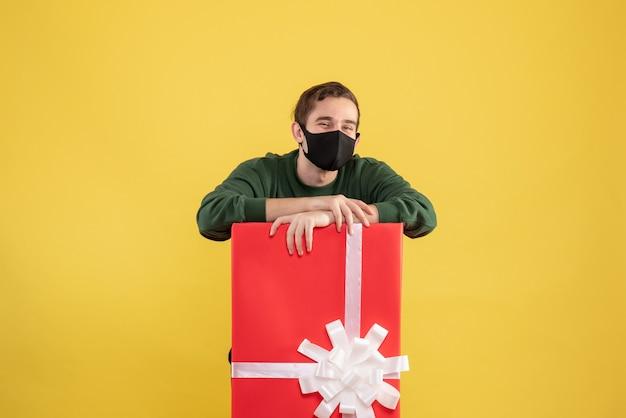 Giovane di vista frontale con la maschera nera che sta dietro il grande giftbox su giallo Foto Gratuite