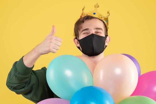 Вид спереди молодого человека с короной и черной маской, делая большой палец вверх знак на желтом Бесплатные Фотографии