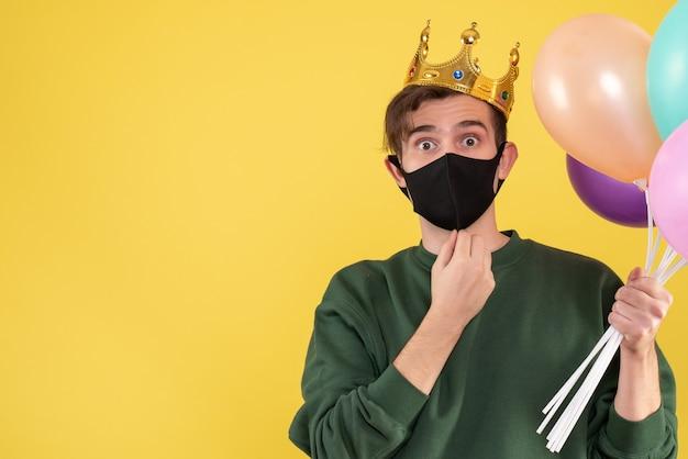 Giovane vista frontale con corona e maschera nera che tiene palloncini su giallo Foto Gratuite