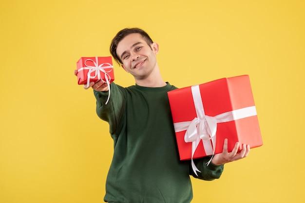 Вид спереди молодой человек в зеленом свитере, дающий рождественский подарок, стоя на желтом Бесплатные Фотографии