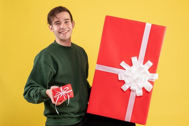 Вид спереди молодой человек с зеленым свитером, держащий большие и маленькие подарки, стоящий на желтом Бесплатные Фотографии