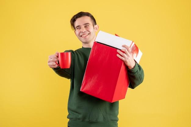 Вид спереди молодой человек с зеленым свитером, держащий большой подарок и красную чашку, стоящий на желтом Бесплатные Фотографии