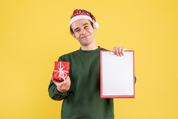 Вид спереди молодой человек с зеленым свитером, держащий буфер обмена и подарок, стоящий на желтом Бесплатные Фотографии