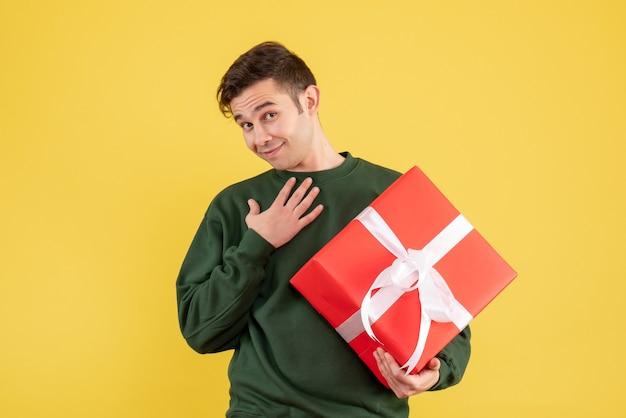 Вид спереди молодой человек с зеленым свитером, держащий подарок, положив руку на грудь на желтом Бесплатные Фотографии