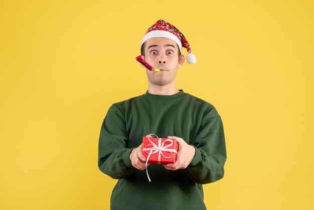 Giovane di vista frontale con il regalo della tenuta del maglione verde facendo uso del noisemaker che sta sul colore giallo Foto Gratuite