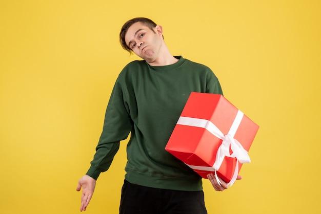 Вид спереди молодой человек с зеленым свитером, держащий подарок на желтом Бесплатные Фотографии