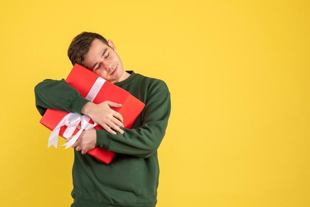 Вид спереди молодой человек с зеленым свитером, крепко держащий свой подарок на желтом Бесплатные Фотографии