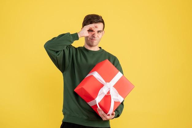 Вид спереди молодой человек с зеленым свитером, держащий рождественский подарок на желтом Бесплатные Фотографии