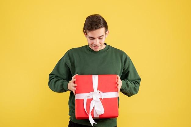 Вид спереди молодой человек в зеленом свитере, глядя на свой подарок на желтом Бесплатные Фотографии