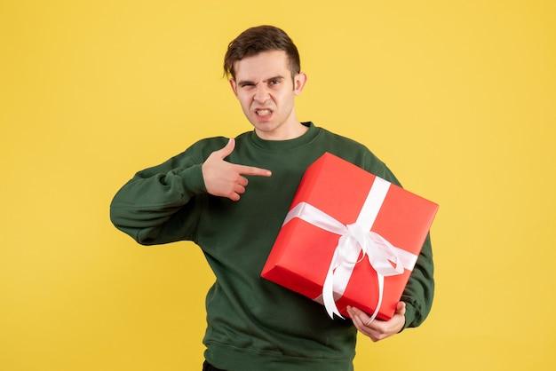 Вид спереди молодой человек с зеленым свитером, указывая на подарок на желтом Бесплатные Фотографии