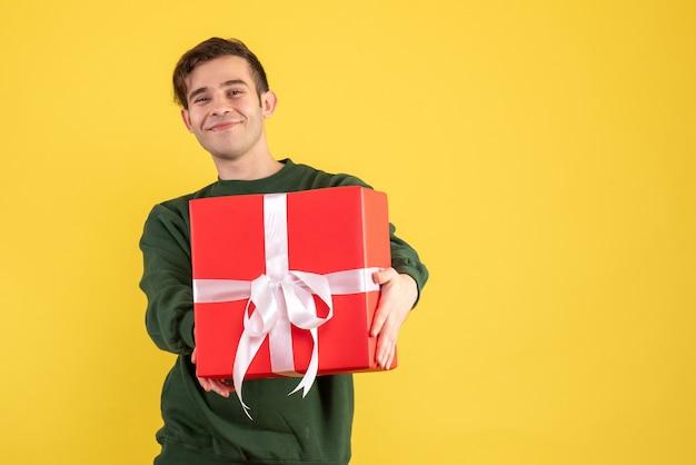 Вид спереди молодой человек с зеленым свитером, показывающий свой подарок на желтом Бесплатные Фотографии
