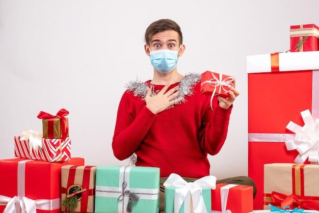 Вид спереди молодой человек с маской, держащий подарок, сидящий вокруг рождественских подарков Бесплатные Фотографии