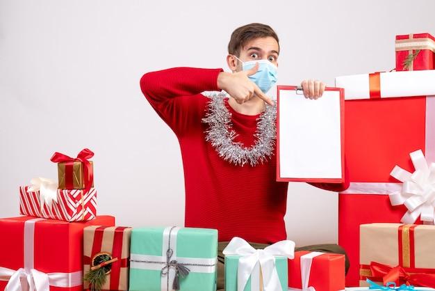 바닥 크리스마스 선물에 앉아 손가락 클립 보드 가리키는 마스크 전면보기 젊은 남자 무료 사진