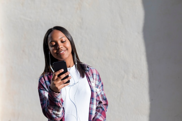 Front view of a young smiling african american woman standing outdoors while smiling and listening music by earphones in a sunny day Premium Photo