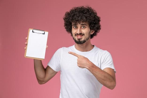 白いtシャツで彼の白いノートを示す正面図の若い学生 無料写真