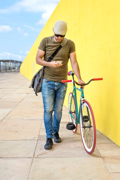 Front view of a young trendy man with a fixed bike Premium Photo