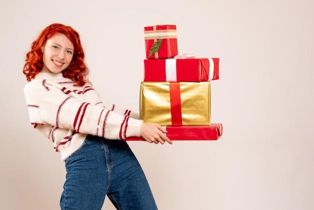 Vista frontale della giovane donna che trasportano i regali di natale sul muro bianco Foto Gratuite