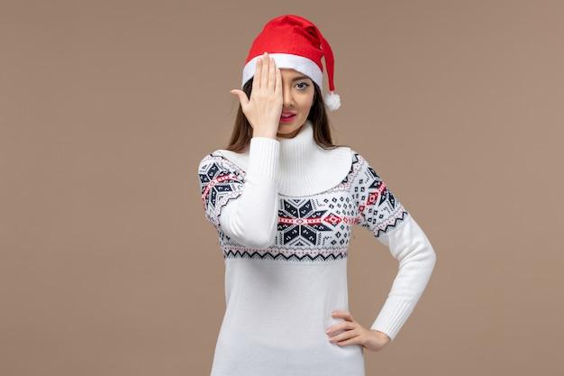 Giovane donna di vista frontale che copre metà del suo viso su uno spazio marrone Foto Gratuite