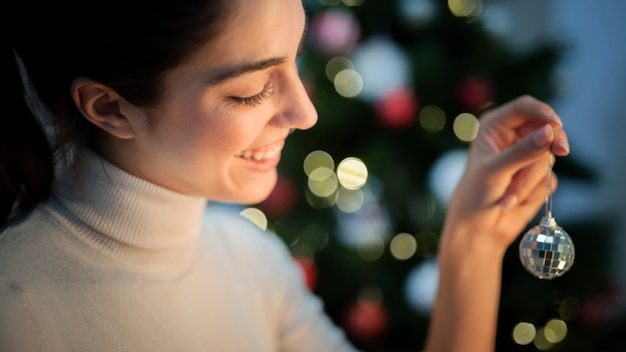 Front view young woman decorating tree with globe Free Photo
