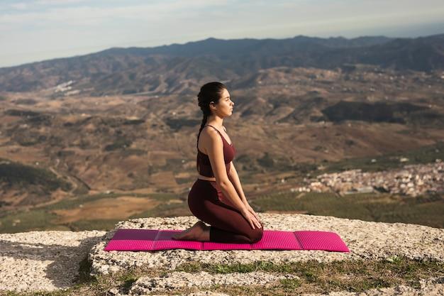 Вид спереди молодая женщина делает йогу Бесплатные Фотографии