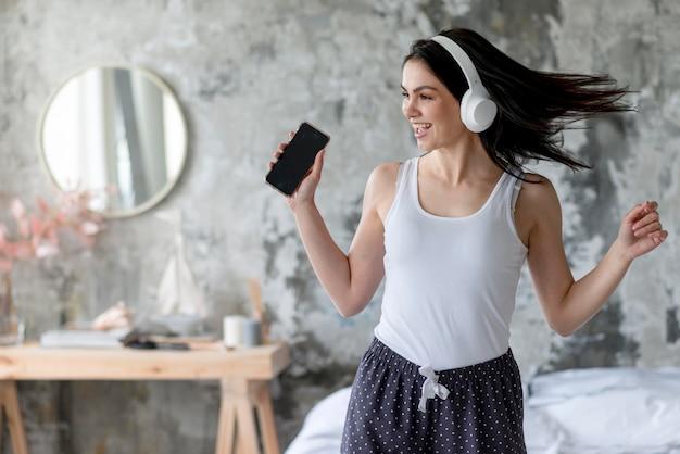 Вид спереди молодая женщина, наслаждаясь слушать музыку Premium Фотографии