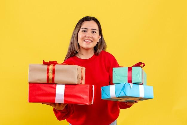 Giovane donna di vista frontale che tiene i regali di natale su fondo giallo Foto Gratuite