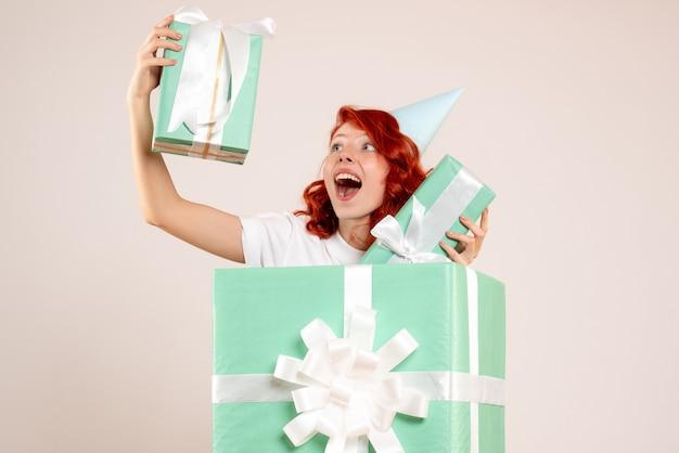 Вид спереди молодая женщина внутри настоящего, держащая другие подарки на белом фоне Бесплатные Фотографии