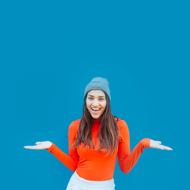 Front view of young woman shrugging her shoulder against blue backdrop Free Photo