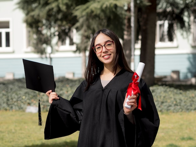 Front view young woman wearing graduation gown Premium Photo