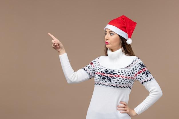 Giovane donna di vista frontale con il mantello rosso sul natale di emozione del nuovo anno del fondo marrone Foto Gratuite