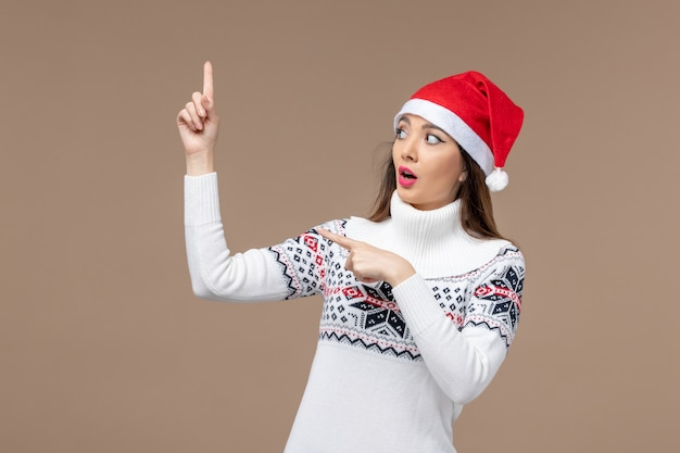 Giovane donna di vista frontale con cappuccio rosso di natale su fondo marrone natale emozioni capodanno Foto Gratuite