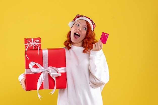 Front view of young woman with xmas presents and bank card on yellow wall Free Photo