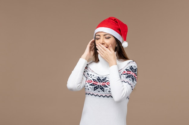 Giovane donna di vista frontale che sbadiglia sul nuovo anno marrone di emozione di natale del fondo Foto Gratuite