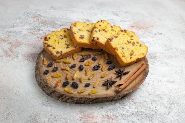 Вкусные кусочки торта с изюмом на светло-белой поверхности, вид спереди Бесплатные Фотографии
