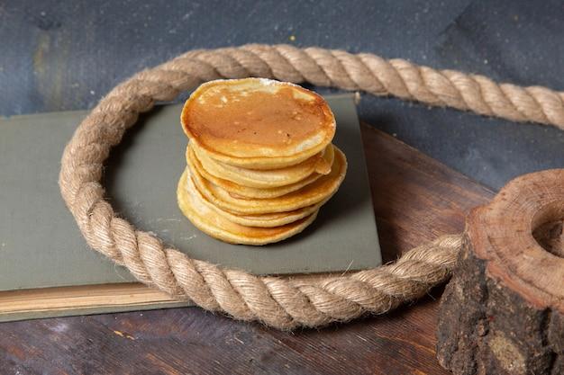 Vista frontale yummy deliziosi muffin con corde sullo sfondo grigio cibo pasto colazione frittelle dolci Foto Gratuite